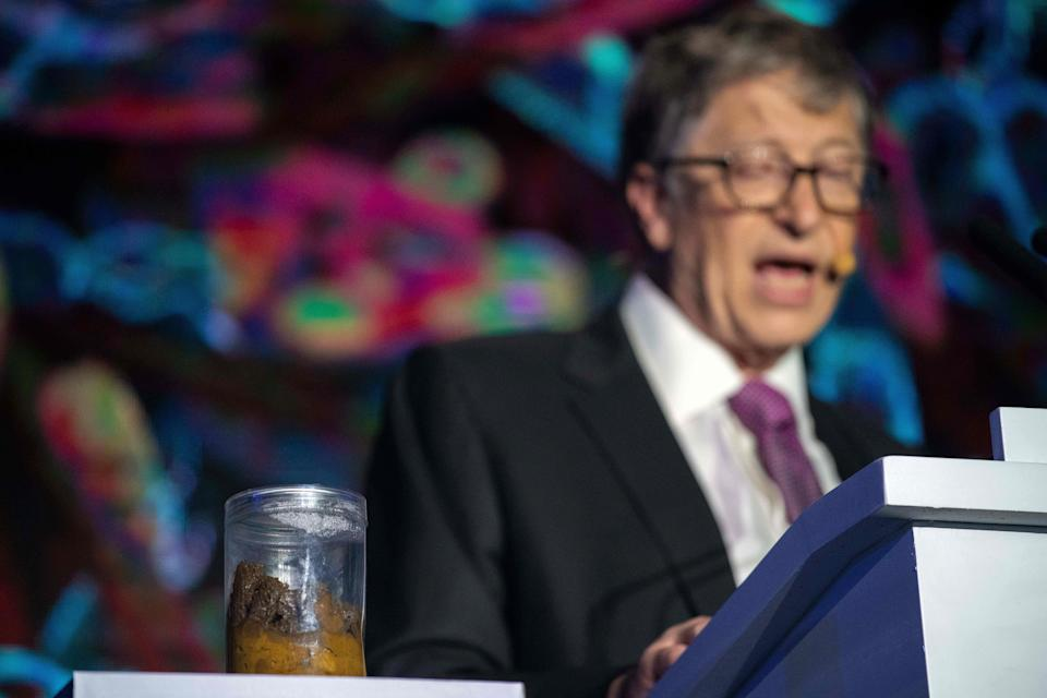 Microsoft founder Bill Gates (R) talks next to a container (L) with human feces during the