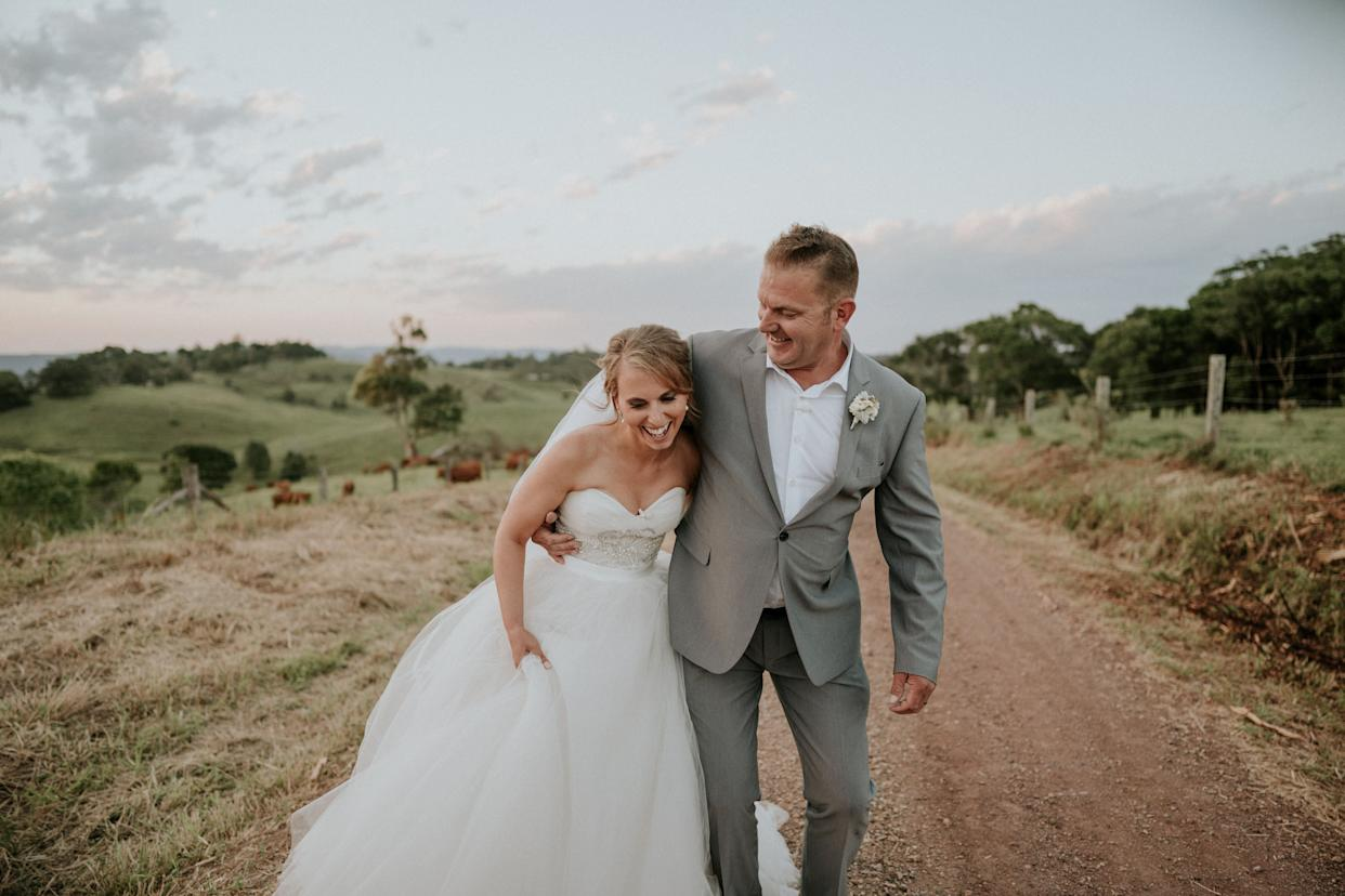 """The bride and groom stand together laughing on a dirt road with green hills and a pale blue, partly cloudy sky behind them. The groom has his arm wrapped around the bride's waist as she holds her skirt in one hand. (Photo: <a href=""""https://www.jamesday.com.au/"""" rel=""""nofollow noopener"""" target=""""_blank"""" data-ylk=""""slk:James Day Photography"""" class=""""link rapid-noclick-resp"""">James Day Photography</a>)"""