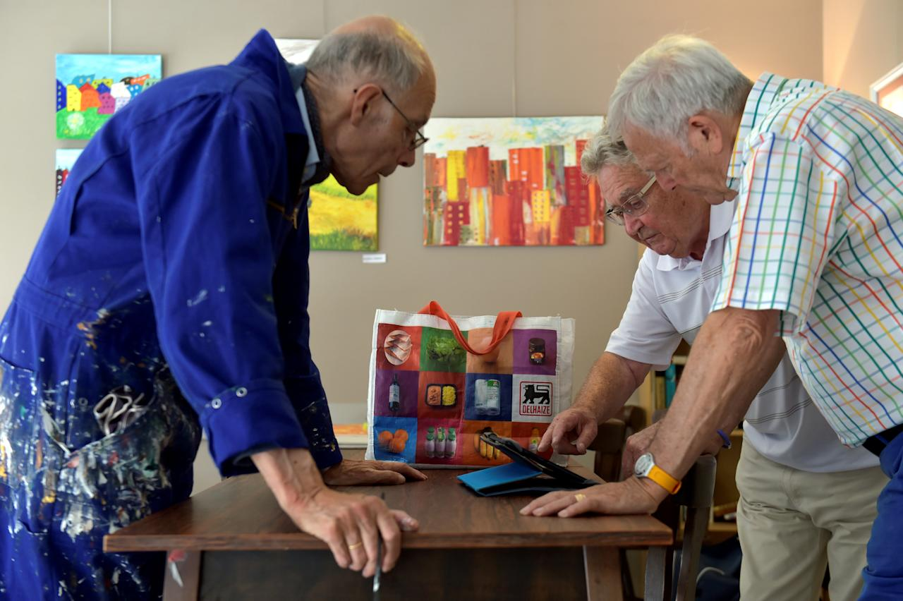 Men looks at a tablet as they work on paintings in a social center in Brussels, Belgium June 26, 2017. REUTERS/Eric Vidal