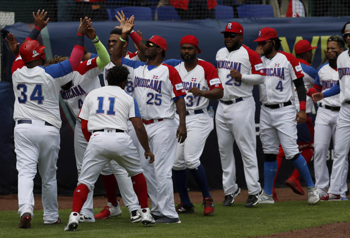 Dominican Republic baseman Juan Francisco, first left, is congratulated by his teammates after scoring a run against Venezuela during a final Olympic baseball qualifier game, in Puebla, Mexico, Saturday, June 26, 2021. (AP Photo/Fernando Llano)