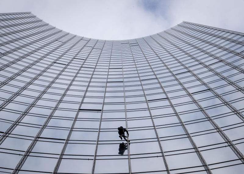 """French urban climber Alain Robert, well known as """"Spiderman"""", climbs up the 'Skyper' highrise in Frankfurt, Germany, Saturday, Sept. 28, 2019. (AP Photo/Michael Probst)"""