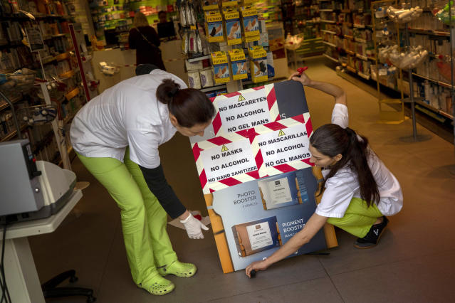 """Pharmacists fix banners reading in Catalan, Spanish and English: """"no masks, no alcohol, no clear hand gel"""" in a pharmacy in Barcelona, Spain, Saturday, March 14, 2020. Spain's prime minister has announced a two-week state of emergency from Saturday in a bid to contain the new coronavirus outbreak. For most people, the new coronavirus causes only mild or moderate symptoms. For some, it can cause more severe illness, especially in older adults and people with existing health problems. (AP Photo/Emilio Morenatti)"""