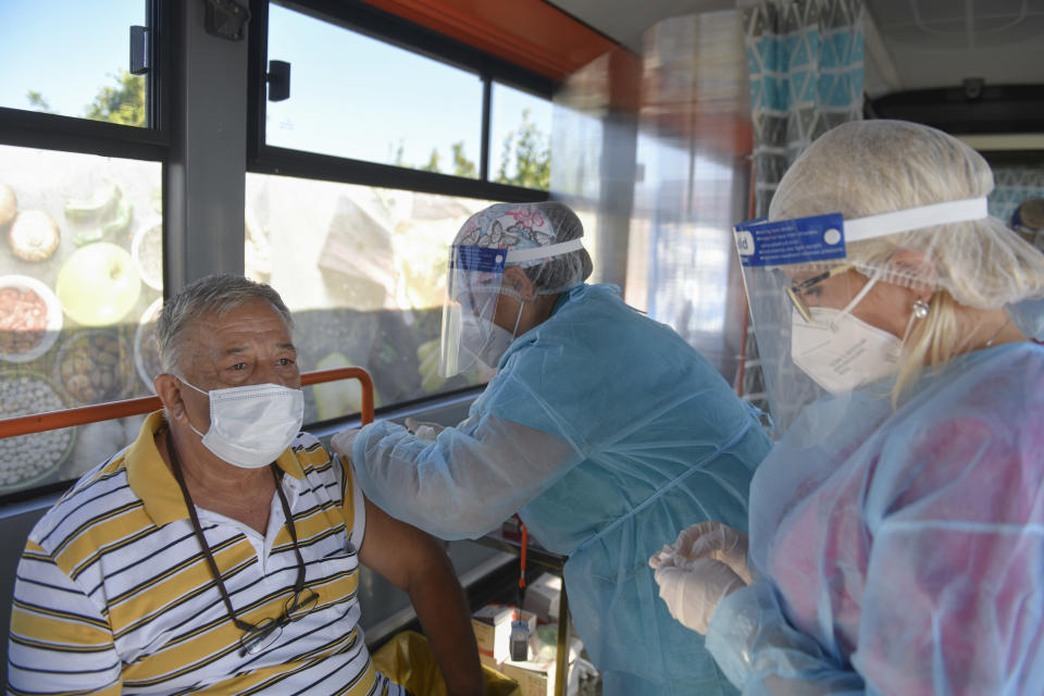 FILE - In this Sept. 4, 2021, file photo, a man receives the Johnson & Johnson vaccine in a bus that serves as a mobile COVID-19 vaccination unit in Bucharest, Romania. In both the U.S. and the EU, officials are struggling with the same question: how to boost vaccination rates to the max and end a pandemic that has repeatedly thwarted efforts to control it. In the European Union, officials in many places are requiring people to show proof of vaccination, a negative test or recent recovery from COVID-19 to participate in everyday activities — even sometimes to go to work. (AP Photo/Andreea Alexandru, File)
