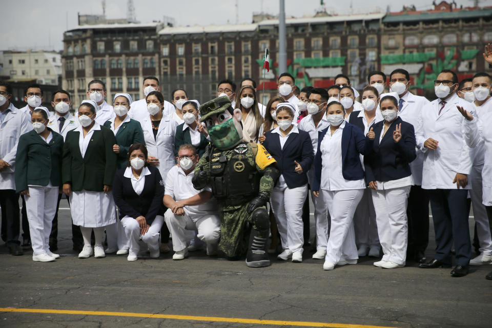 Medical workers who tend to COVID-19 patients and who received a medal from the government as recognition for their efforts pose for a photo with an Army mascot during the annual Independence Day military parade in Mexico City's main square of the capital, the Zócalo, Wednesday, Sept. 16, 2020. Mexico celebrates the anniversary of its independence uprising of 1810. ( AP Photo/Marco Ugarte)