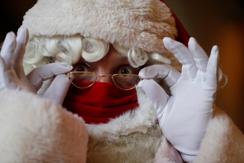 A Santa adjusts his glasses over a face mask as he attends a socially distanced Santa school training at Southwark Cathedral in London (Photo: ASSOCIATED PRESS)