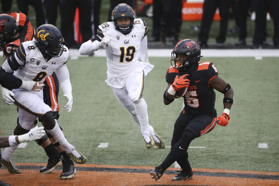 Oregon State running back Jermar Jefferson (6) looks for a path past California inside linebacker Kuony Deng (8) and outside linebacker Cameron Goode (19) during the second half of an NCAA college football game in Corvallis, Ore., Saturday, Nov. 21, 2020. Oregon State won 31-27. (AP Photo/Amanda Loman)