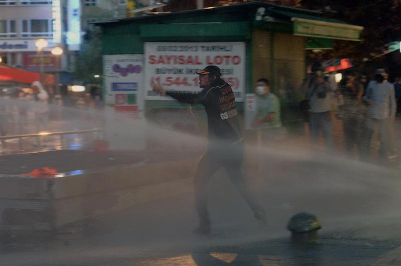 In this photo taken late Wednesday, June 5, 2013, a Turkish protester clashes with riot police in Ankara, Turkey. All eyes were turned on Turkish Prime Minister Recep Tayyip Erdogan for signs of a mellowed tone as he returns from a four-day tour of North Africa to his country hit by nearly a week of anti-government protests. (AP Photo)
