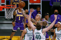 Los Angeles Lakers' Kyle Kuzma (0) goes to basket while defended by Boston Celtics' Luke Kornet (40) during the second half of an NBA basketball game Thursday, April 15, 2021, in Los Angeles. (AP Photo/Ringo H.W. Chiu)