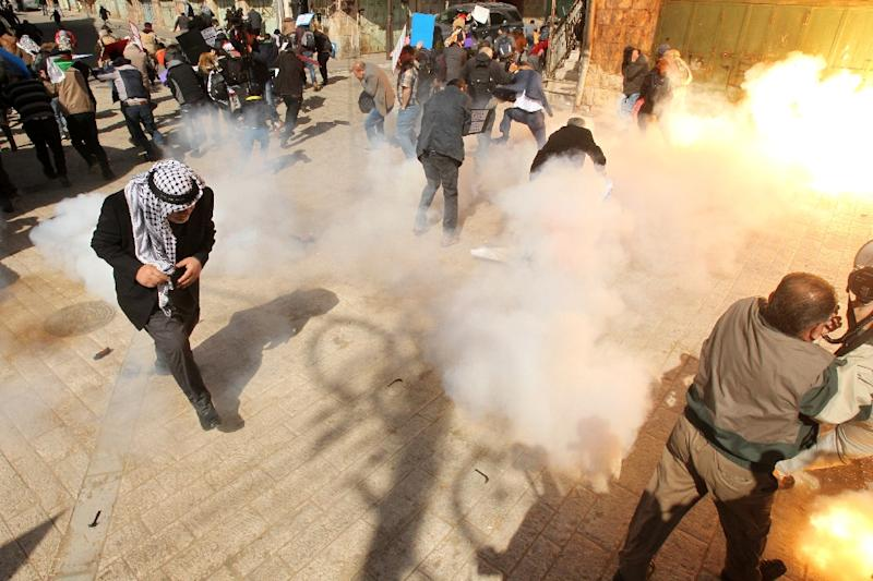 Protesters take cover from smoke and flames as Israeli soldiers fire stun grenades and tear gas during clashes in Hebron on February 20, 2016 (AFP Photo/Hazem Bader)
