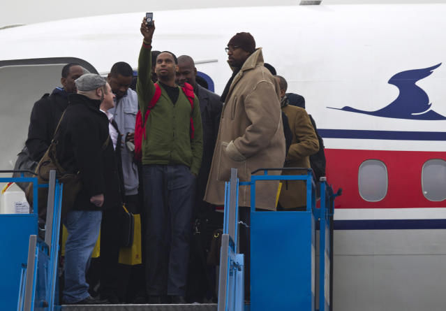 "U.S. basketball player Jerry Dupree, center, uses a mobile camera to take a photograph as he and fellow players including former NBA player Vin Baker, right, arrive at the international airport in Pyongyang, North Korea, Monday, Jan. 6, 2014. Dennis Rodman arrived in the North Korean with a squad of former basketball stars in what Rodman calls ""basketball diplomacy,"" although U.S. officials have criticized his efforts. (AP Photo/Kim Kwang Hyon)"