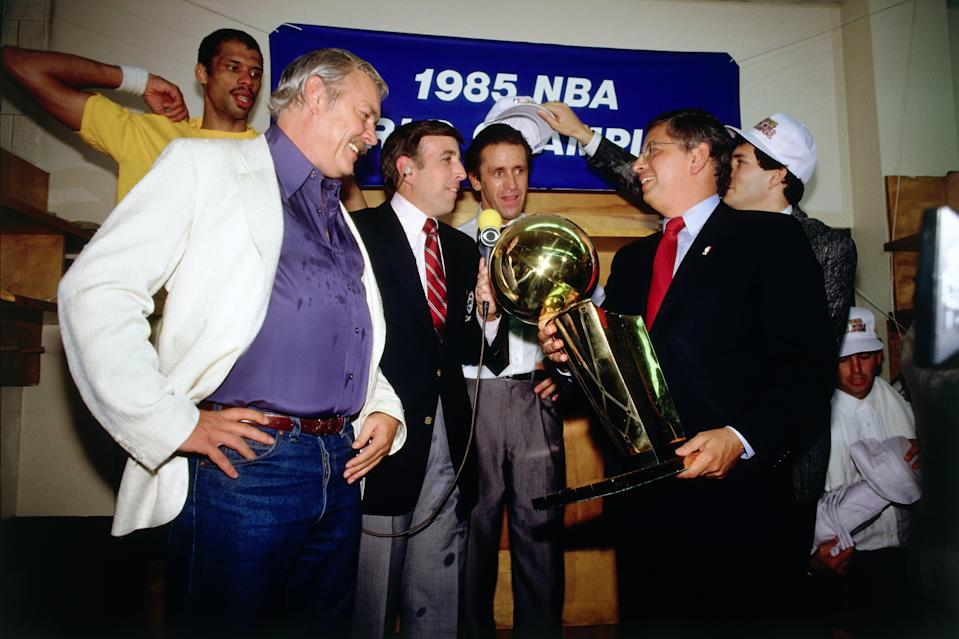 NBA Commissioner David Stern presents the championship trophy to Lakers owner Jerry Buss while the Los Angeles Lakers celebrate in the locker room after winning the 1985 NBA Finals against the Boston Celtics on June 9, 1985 in Boston, Massachusetts. Lakers 111 vs Celtics 100. (Photo by Andrew D. Bernstein/NBAE via Getty Images)