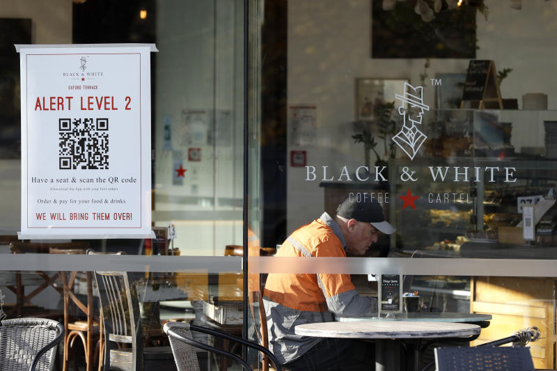 A man enjoys coffee in a cafe in Christchurch, New Zealand, Thursday, May 14, 2020. New Zealand lifted most of its remaining lockdown restrictions from midnight Wednesday as the country prepares for a new normal. Malls, retail stores and restaurants are all reopening Thursday in the South Pacific nation of 5 million, and many people are returning to their workplaces. (AP Photo/Mark Baker)