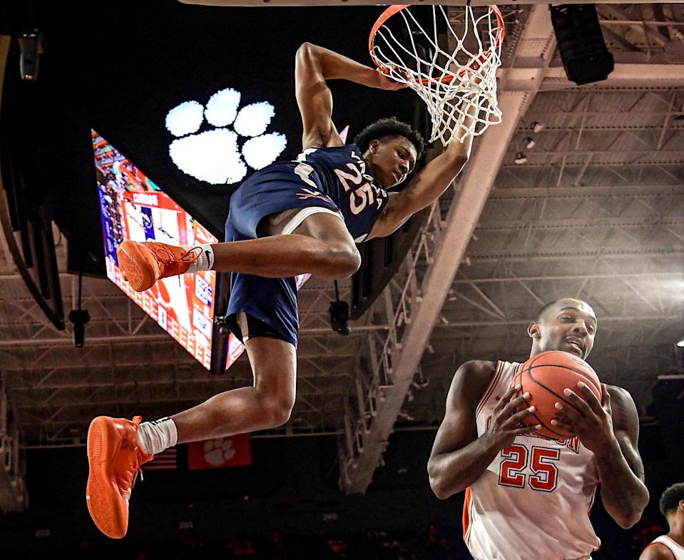 Jan 16, 2021; Clemson, South Carolina, USA; Virginia Cavaliers guard Trey Murphy III (25) hangs on the rim after dunking against Clemson Tigers forward Aamir Simms (right) during the second half at Littlejohn Coliseum.