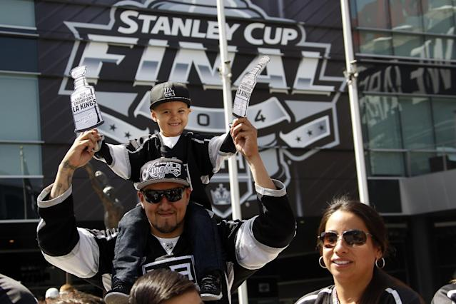 Los Angeles Kings NHL hockey fans cheer as the team make their way during a parades with the Stanley Cup trophy downtown Los Angeles, Monday, June 16, 2014. The parade and rally were held to celebrate the Kings' second Stanley Cup championship in three seasons. The Kings defeated the New York Rangers for the title. (AP Photo/Nick Ut)