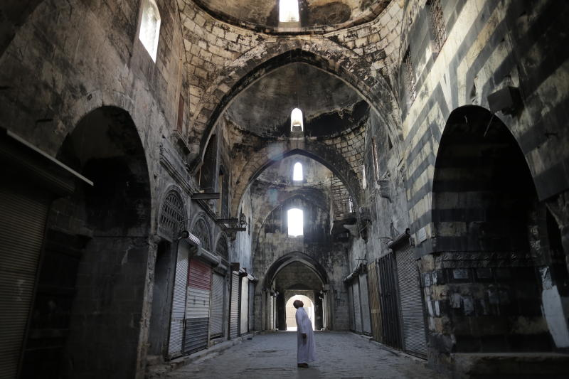 In this Saturday, July 27, 2019 photo, a Syrian man checks a market in the old city of Aleppo, Syria. Much of Aleppo's centuries-old covered market is still in ruins but slowly small parts of it have been renovated where business is slowly coming back to normal nearly three years after major battles in Syria's largest city and once commercial center came to an end. (AP Photo/Hassan Ammar)