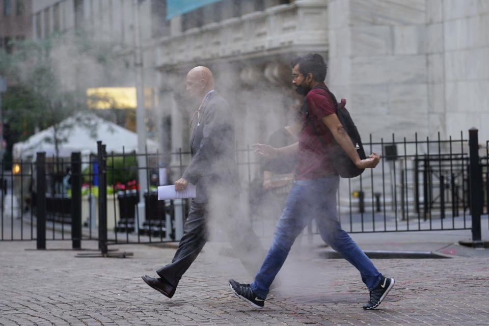 FILE - In this June 16, 2021 file photo, people walk through steam from a street grating during the morning commute in New York. Companies around the U.S. are scrambling to figure out how to bring employees back to the office after more than a year of them working remotely. Most are proceeding cautiously, trying to navigate declining COVID-19 infections against a potential backlash by workers who are not ready to return. (AP Photo/Richard Drew)