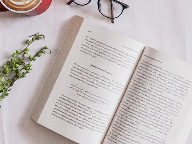 An open book on a table next to glasses