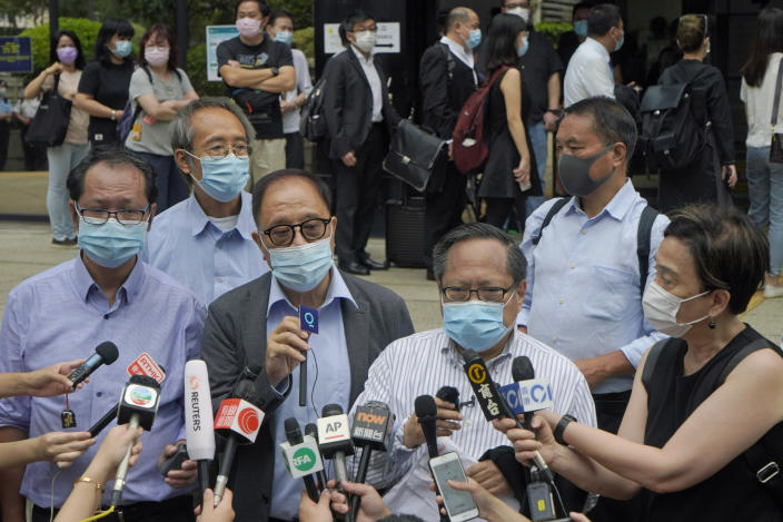 """Various defendants including pro-democracy activists, from left in front, Richard Tsoi, Yeung Sum and Albert Ho speak to media outside a court in Hong Kong, Monday, May 17, 2021. Trial starts for Jimmy Lai and nine others, accused of """"incitement to knowingly take part in an unauthorized assembly"""" for a protest march on Oct. 1, 2019. The court has estimated 10 days for this trial. (AP Photo/Kin Cheung)"""