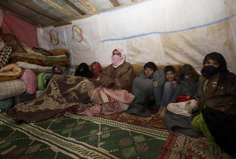 Abu Ali (centre), 60-years old, who fled the violence in Syria's northern Raqa province, sits with some of his 14 children covered in blankets to stay warm in a tent at the unofficial refugee camp in al-Saadiyeh (AFP Photo/Anwar Amro)