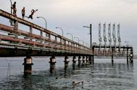 Youths jump into the Red Sea water off an abandoned oil jetty in Israel's southern port city of Eilat