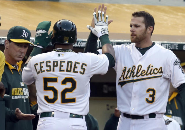 Oakland Athletics' Yoenis Cespedes (52) is congratulated by manager Bob Melvin, left, and Craig Gentry, right, after Cespedes scored against the San Francisco Giants in the third inning of a baseball game against the San Francisco Giants Tuesday, July 8, 2014, in Oakland, Calif. (AP Photo/Ben Margot)