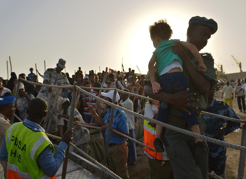 A Djibouti security official carries a young girl down a gangway as people fleeing Yemen arrive aboard a dhow on April 14, 2015 at a the port of Djibouti (AFP Photo/Tony Karumba)