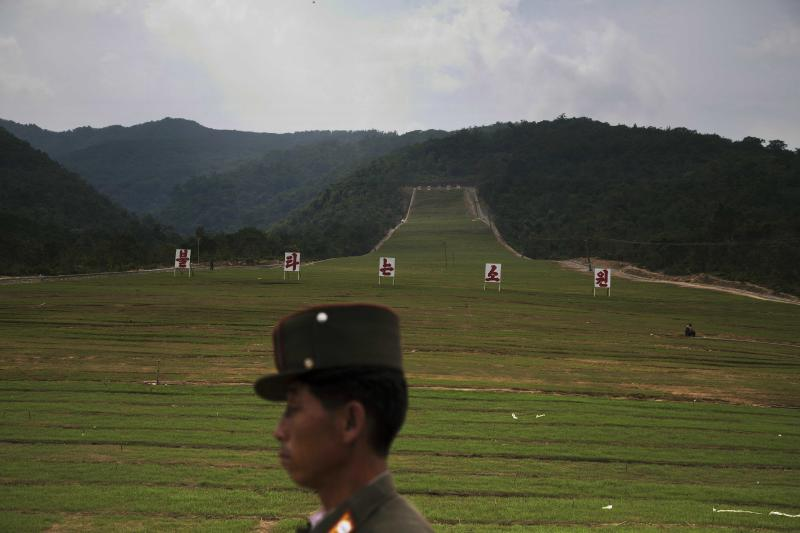 """In this Friday Sept. 20, 2013 photo, a North Korean soldier passes by a ski slope under construction at North Korea's Masik Pass. The signs on the slope together reads """"Burning Hope."""" North Korean authorities have been encouraging a broader interest in sports in the country, calling it """"the hot wind of sports blowing through Korea."""" (AP Photo/David Guttenfelder)"""