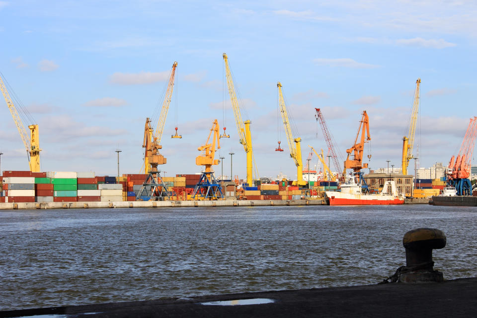 Conceptual image on trade and export of goods at the port. View of the bay, the cranes and containers.