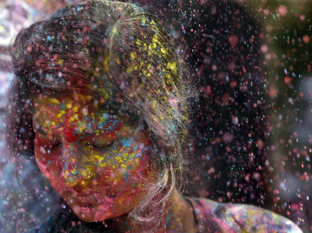 In this Thursday, March 21, 2019, file photo, revelers throw colored powder on a woman during celebrations marking Holi, the Hindu festival of colors, in Mumbai, India. (AP Photo/Rajanish Kakade, File)