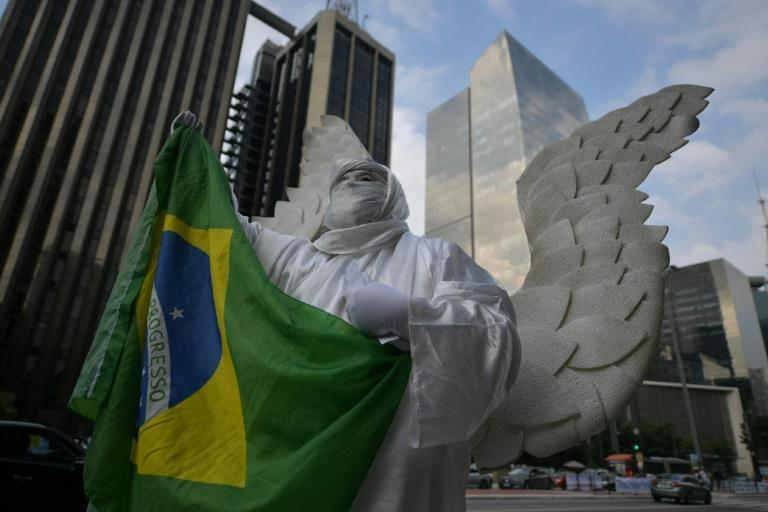 A person disguised as an angel holds a Brazilian flag during a demo in support of Brazilian President Jair Bolsonaro in Sao Paulo on May 15, 2021