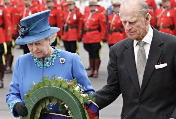 Queen Elizabeth II and Prince Philip place a wreath during a memorial for the four Mounties gunned down in rural Alta., on May 19, 2005, in Regina.