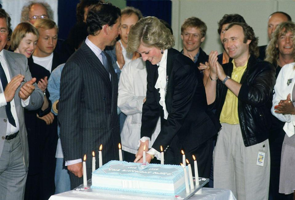 <p>Prince Charles, Princess Diana, and singer Phil Collins gathered around a blue cake to celebrate ten years of the Prince's Trust Concert at Wembley. </p>