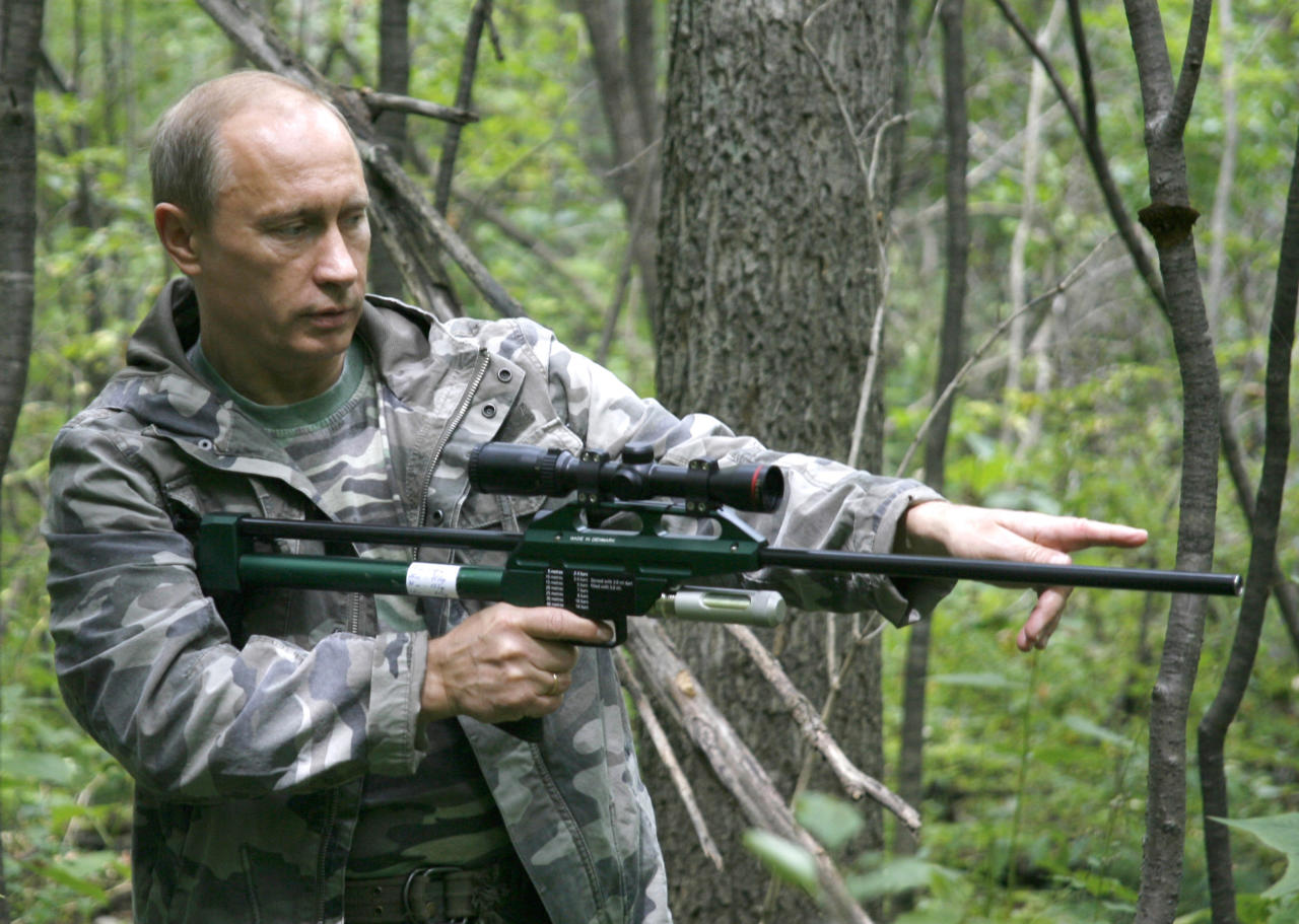 In this Sunday, Aug. 31, 2008 file pool photo then Prime Minister Vladimir Putin holds a tranquilizer gun  in a Russian Academy of Sciences reserve in Russia's Far East. Putin has become alternately notorious and beloved for an array of adventurous stunts, including posing with a tiger cub and riding a horse bare-chested. (AP Photo/RIA Novosti, Alexei Druzhinin, POOL, file)