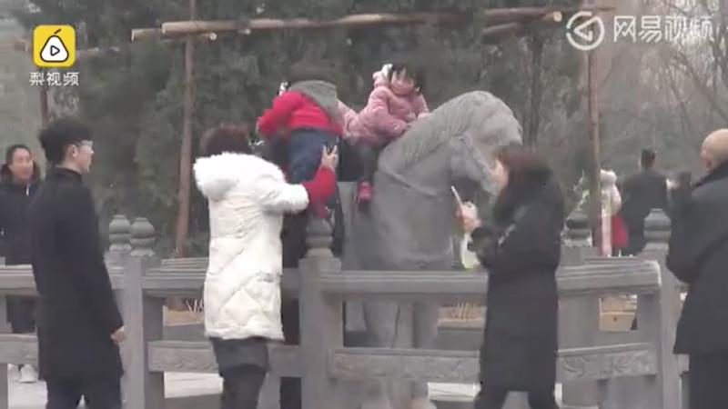 Chinese tourists ignore warnings, clamber over ancient horse statues