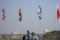 """A man wearing a face mask against the coronavirus drives past flags, from left, of the United States, United Arab Emirates, Israel and Bahrain at the Peace Bridge in Netanya, Israel, Monday, Sept. 14, 2020. For the first time in more than a quarter-century, a U.S. president will host a signing ceremony between Israelis and Arabs at the White House, billing it as an """"historic breakthrough"""" in a region long known for its stubborn conflicts. (AP Photo/Ariel Schalit)"""
