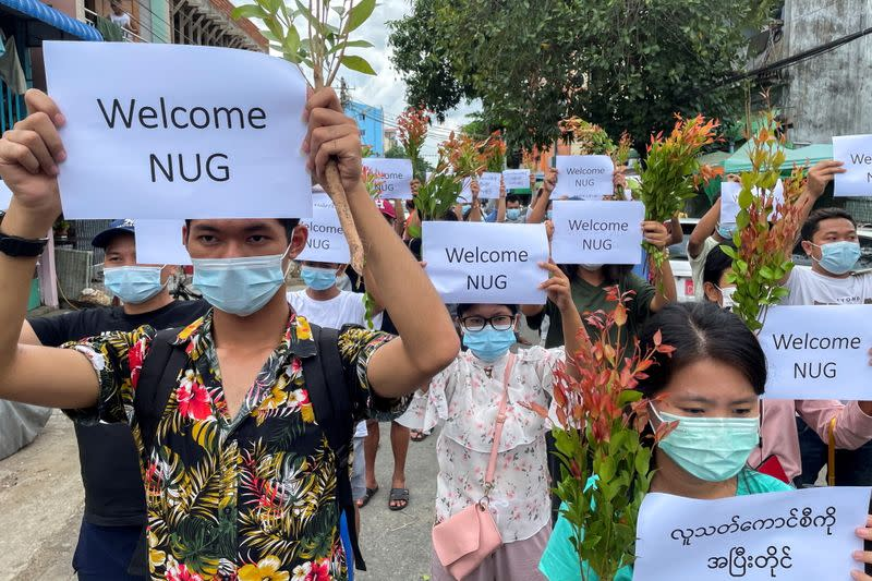 FILE PHOTO: Anti-government protesters hold placards to show their support and welcome the new National Unity Government found by ousted NLD legislators and call to continue strike from traditional new year in Myanmar, in Yangon