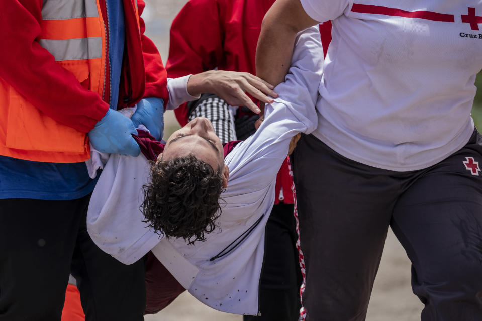 A migrant is carried by Spanish Red Cross members after crossing near the border of Morocco and Spain, at the Spanish enclave of Ceuta, on Tuesday, May 18, 2021. Ceuta, a Spanish city of 85,000 in northern Africa, faces a humanitarian crisis after thousands of Moroccans took advantage of relaxed border control in their country to swim or paddle in inflatable boats into European soil. (AP Photo/Bernat Armangue)