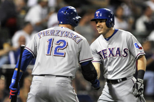 Texas Rangers' Ian Kinsler right, celebrates with teammate A.J. Pierzynski (12), at home plate after hitting an inside-the-park home run during the third inning of a baseball game against the Chicago White Sox in Chicago, Friday, Aug. 23, 2013. (AP Photo/ Paul Beaty)