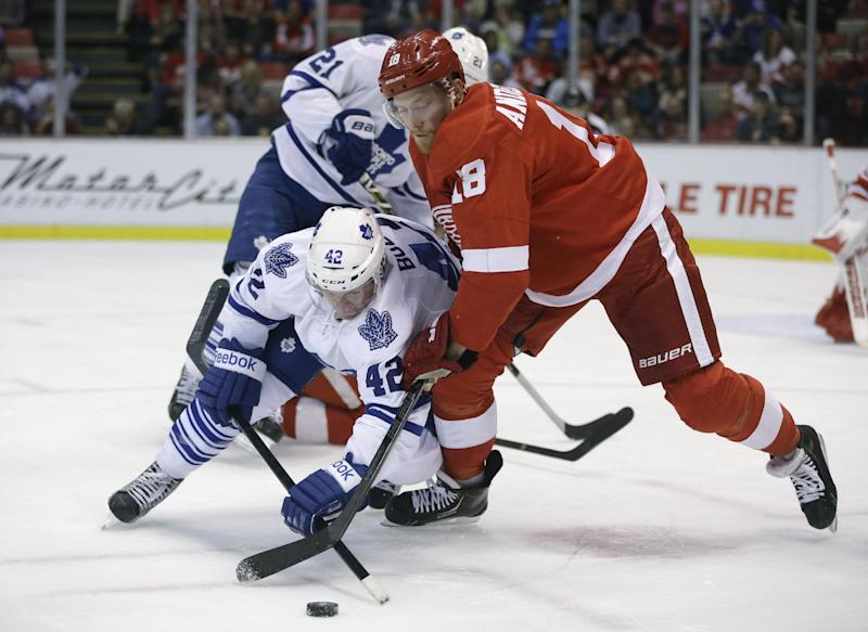 Toronto Maple Leafs center Tyler Bozak (42) and Detroit Red Wings center Joakim Andersson (18) of Sweden chase the puck during the first period of an NHL hockey game in Detroit, Friday, Sept. 27, 2013. (AP Photo/Carlos Osorio)