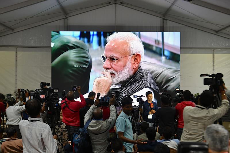 Members of the media cover the development as India's Prime Minister Narendra Modi is seen on a tv.