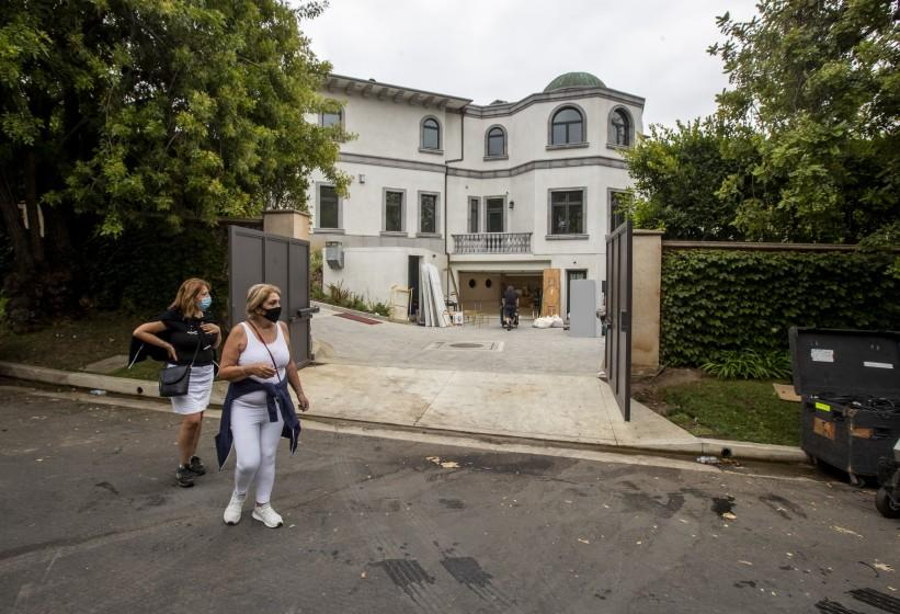 HOLMBY HILLS, CA - AUGUST 06: Passersby watch as party rental crews pack up at the scene of a wedding at 10350 Wyton Drive on Thursday, Aug. 6, 2020 in Holmby Hills, CA. Police reacting to noise complaints shut down the wedding reception after receiving multiple noise complaints Wednesday night.(Brian van der Brug / Los Angeles Times)
