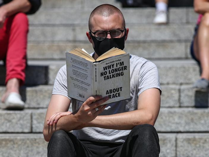 """A masked protester sits to read British writer Reni Eddo-Lodge's book """"Why I'm No Longer Talking to White People About Race."""""""