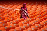 A worker cleans seats in the stands at Sardar Patel Gujarat Stadium, in Ahmedabad