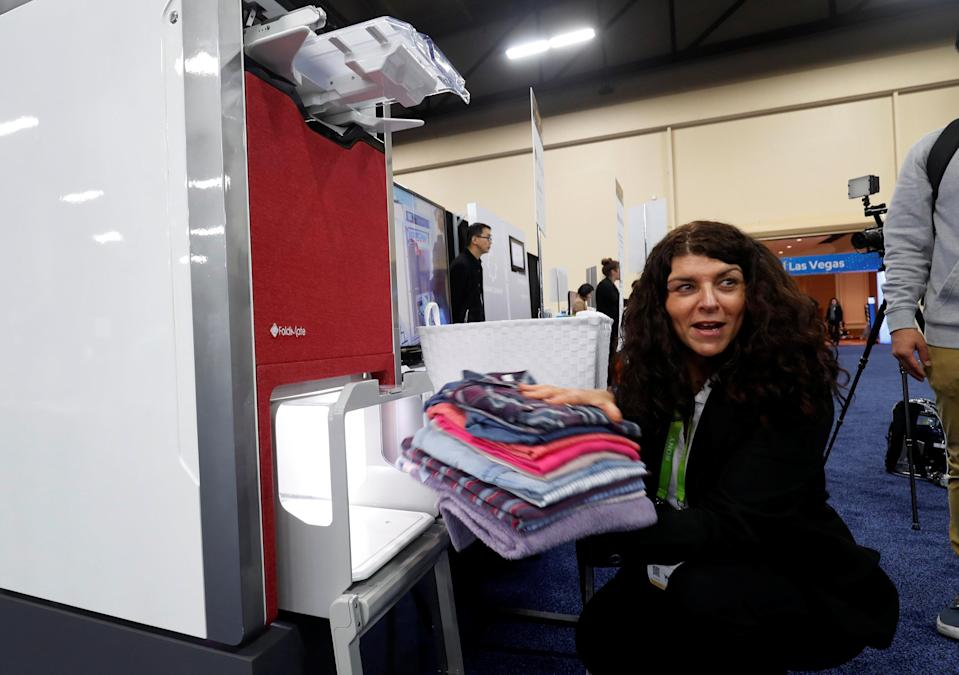 Debbie Cohen-Abravanel, CMO at FoldiMate, takes folded laundry from a FoldiMate automatic laundry folding machine, during CES Unveiled at the 2018 CES in Las Vegas, Nevada, U.S. January 7, 2018. REUTERS/Steve Marcus
