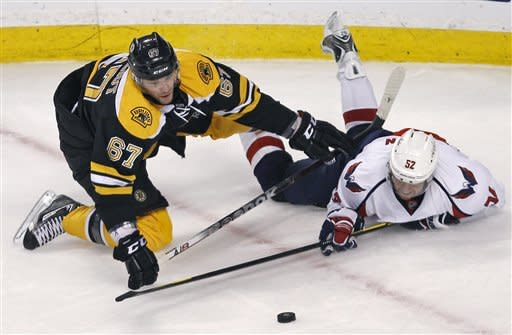 Washington Capitals defenseman Mike Green, right, tries to get a stick on the puck after being dropped to the ice by Boston Bruins left wing Benoit Pouliot (67) during the third period of Game 2 of an NHL hockey Stanley Cup first-round playoff series in Boston, Saturday, April 14, 2012. AP Photo/Charles Krupa)