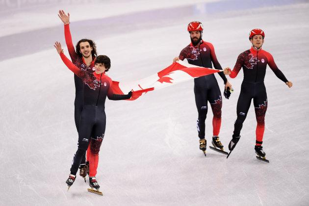 Samuel Girard, Charles Hamelin, Charlie Cournoyer and Pascal Dion of Canada celebrate winning the bronze medal in the 5,000-metre short-track relay.