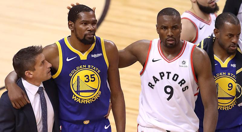 TORONTO, ONTARIO - JUNE 10: Kevin Durant #35 of the Golden State Warriors is consoled by Serge Ibaka #9 of the Toronto Raptors after sustaining an injury in the first half during Game Five of the 2019 NBA Finals at Scotiabank Arena on June 10, 2019 in Toronto, Canada. NOTE TO USER: User expressly acknowledges and agrees that, by downloading and or using this photograph, User is consenting to the terms and conditions of the Getty Images License Agreement. (Photo by Claus Andersen/Getty Images)