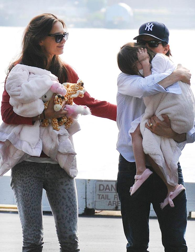 """The family stayed on the move, arriving in New York on Monday. But Tom, Katie, and Suri didn't have to worry about traffic between the airport and Manhattan since they took the high road -- a helicopter. Little Suri, however, clearly didn't like how loud the chopper was. <a href=""""http://www.splashnewsonline.com"""" target=""""new"""">Splash News</a> - August 8, 2011"""