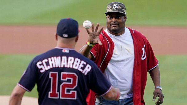 PHOTO: U.S. Capitol Police officer Eugene Goodman catches the ball from Washington Nationals' Kyle Schwarber after throwing out the first pitch before the Washington Nationals baseball game against the New York Mets, Friday, June 18, 2021, in Washington. (Carolyn Kaster/AP)