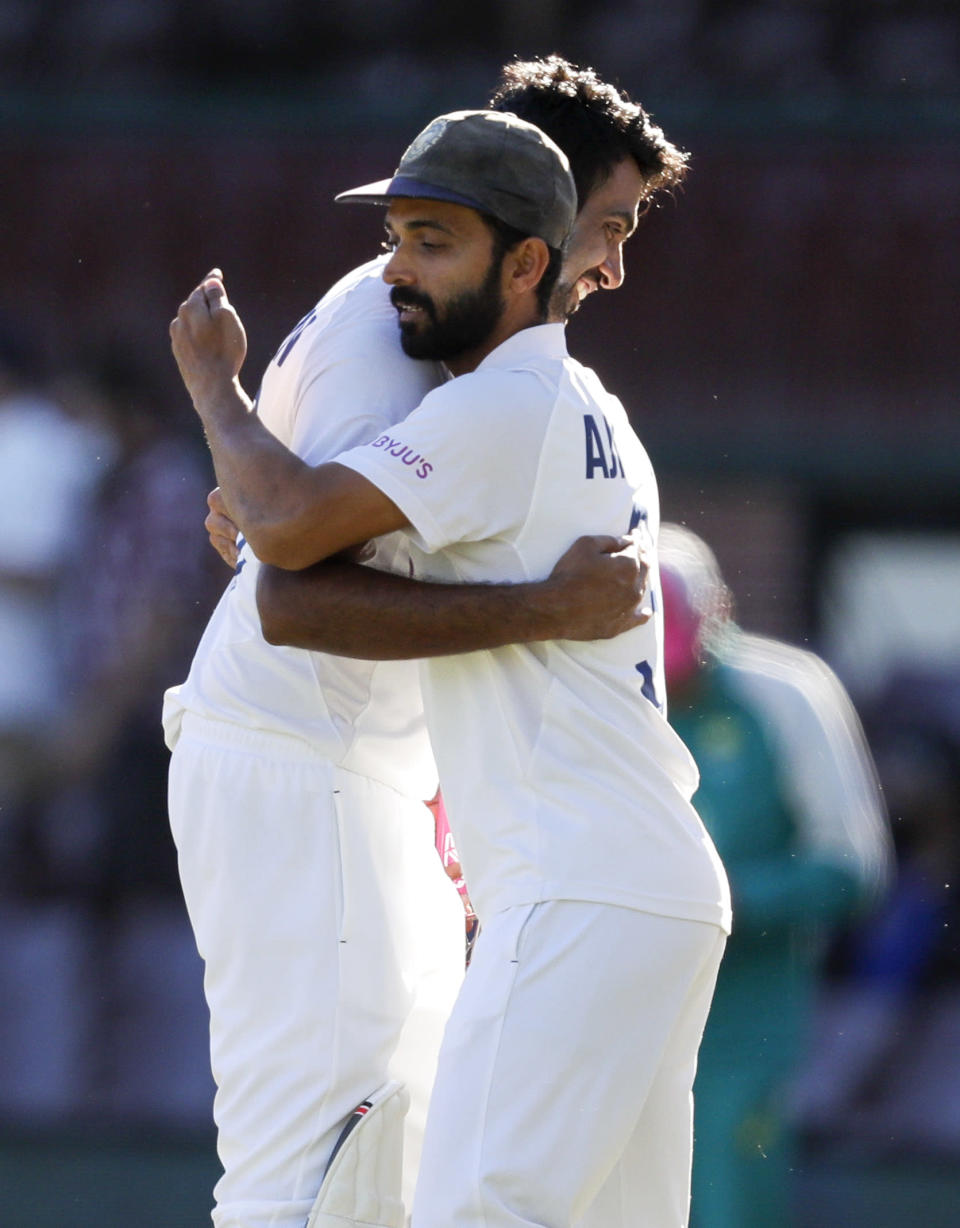 India's Ravichandran Ashwin is embraced by his captain Ajinkya Rahane, left, following play on the final day of the third cricket test between India and Australia at the Sydney Cricket Ground, Sydney, Australia, Monday, Jan. 11, 2021. The test ended in a draw and the series is at 1-1 all with one test to play. (AP Photo/Rick Rycroft)